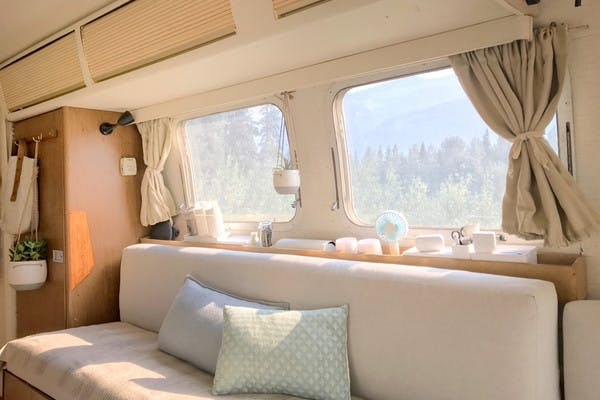 Interior shot of an RV, with cream colored couch, hanging plants and beige curtains, and pine trees outside the window.