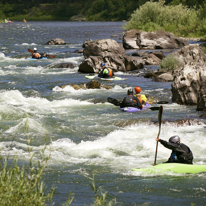 Participants rush down the Blackfoot River in their kayaks.