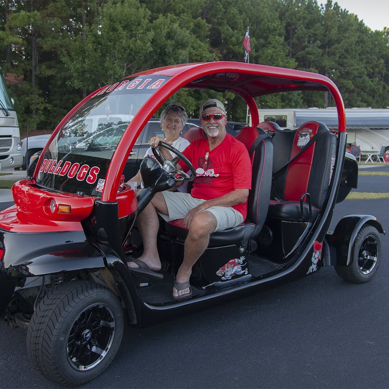 An older man and a woman inside a tricked-out red golf cart, perfect for tailgating.