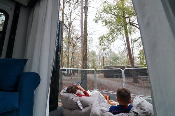 Two young boys sitting in beanbag chairs on an RV patio, looking at the trees around them.