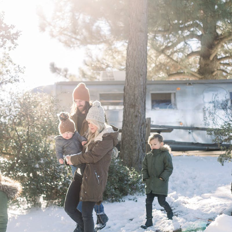 Image of Amber Thrane and her family walking in a snowy forrest, with their Airstream Travel Trailer RV in the background.