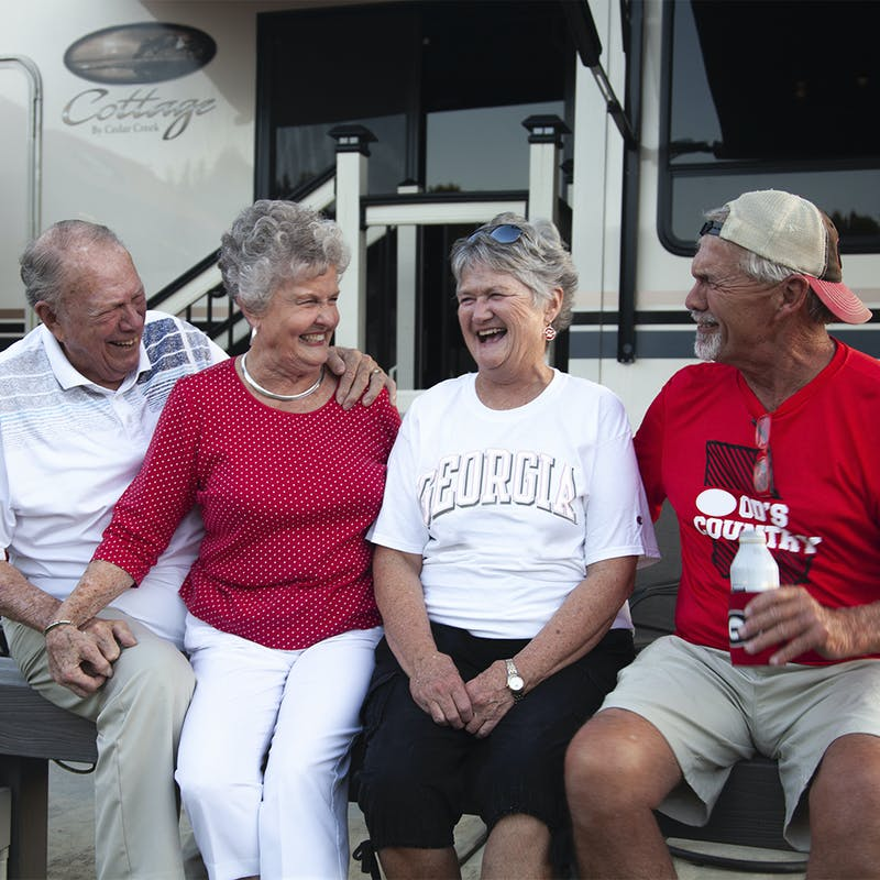Group of elder friends laughing together in front of RV.