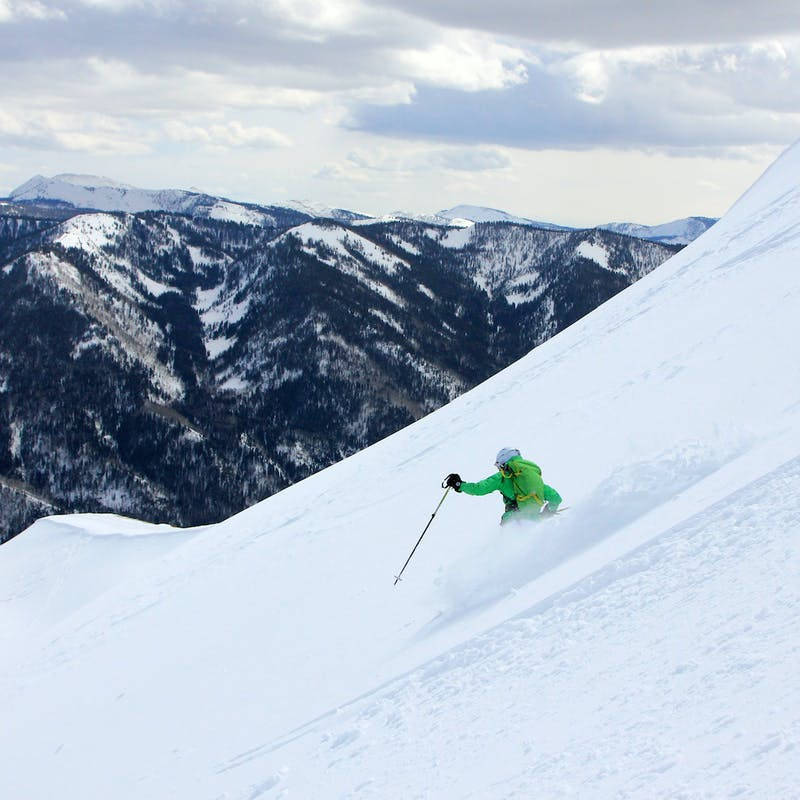 Man in green jacket skis down steep snowy mountain with dark mountains in the background