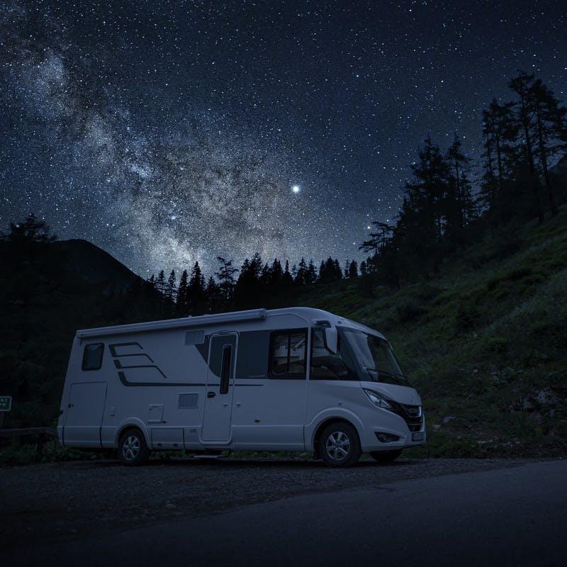 Hymer Class B RV sits underneath the dark, starry sky.