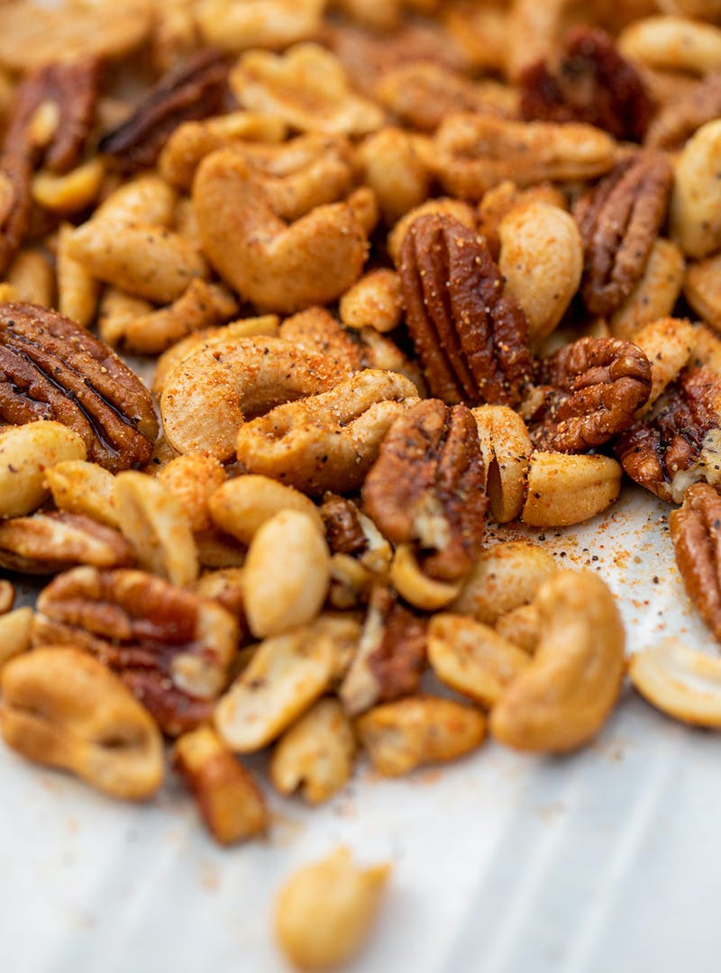 A close up shot of mixed nuts covered in Cajun spices.