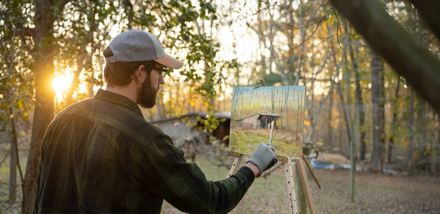 Todd Schabel painting an old barn as the sun goes down through trees.