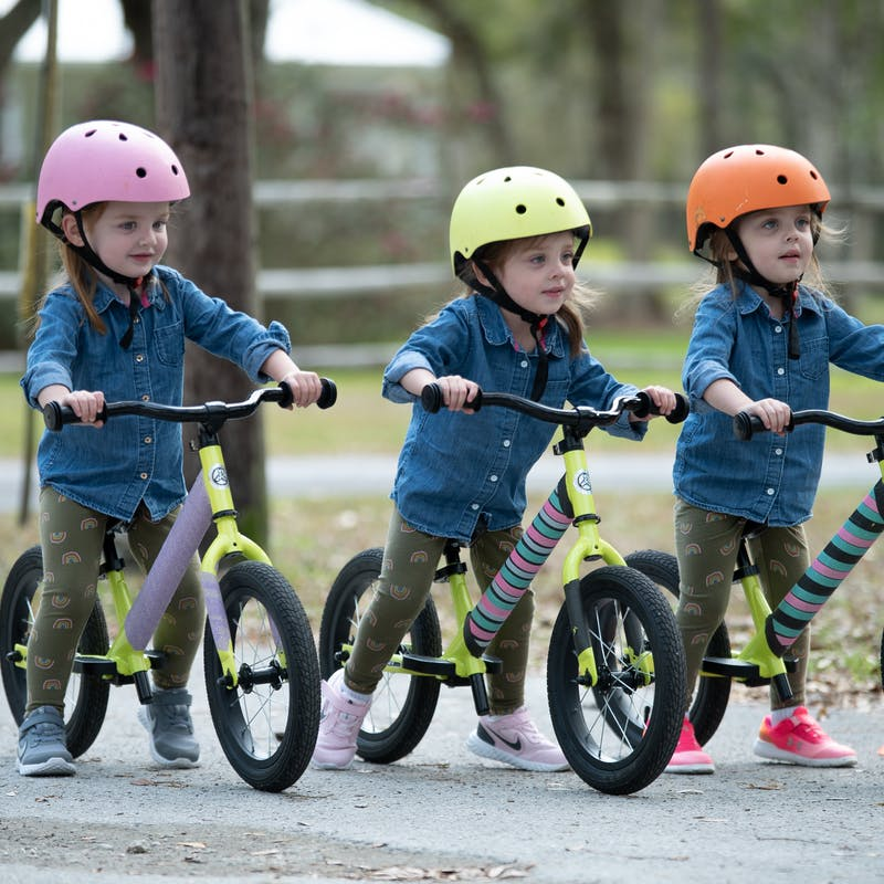 Triplet little girls riding bikes with color coded helmets on their heads.