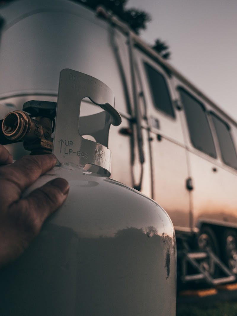 A close up shot of a hand on a propane tank with the sun setting on an RV in the background.