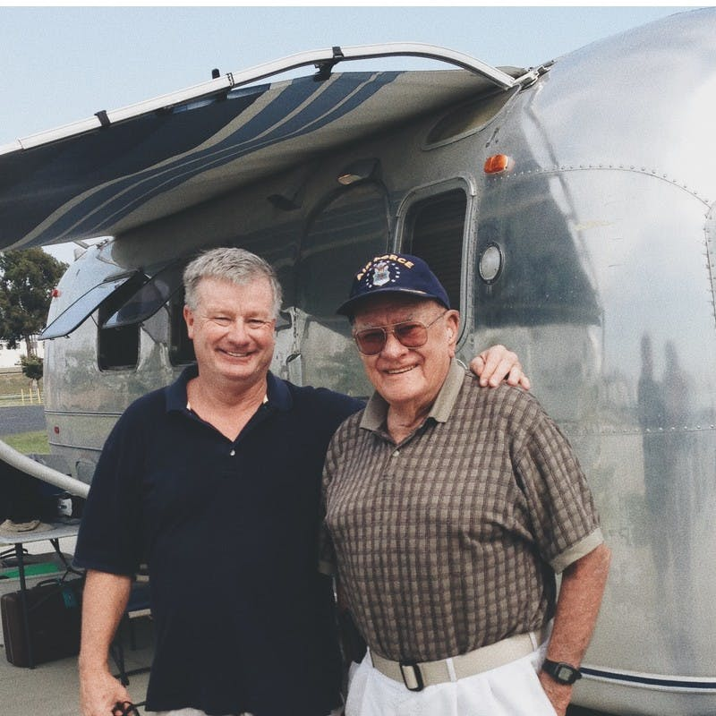 Billy and Grandpa Al standing in front of Airstream travel trailer.
