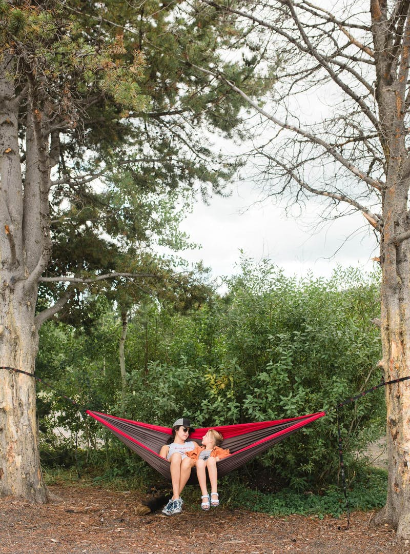 Woman and young girl sit in red hammock