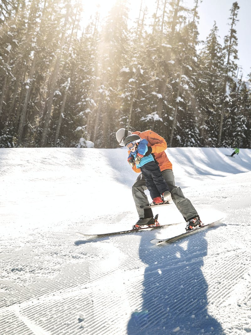 A father lifts his son as they ski down a snowy mountain in Washington.