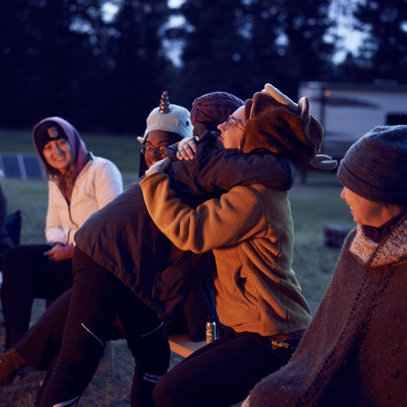 Participants hug one another at their nightly campfire.
