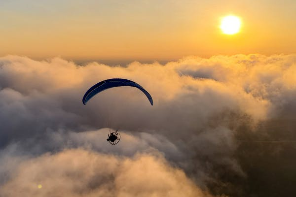 Tucker Gott paramotors over the clouds at sunset.