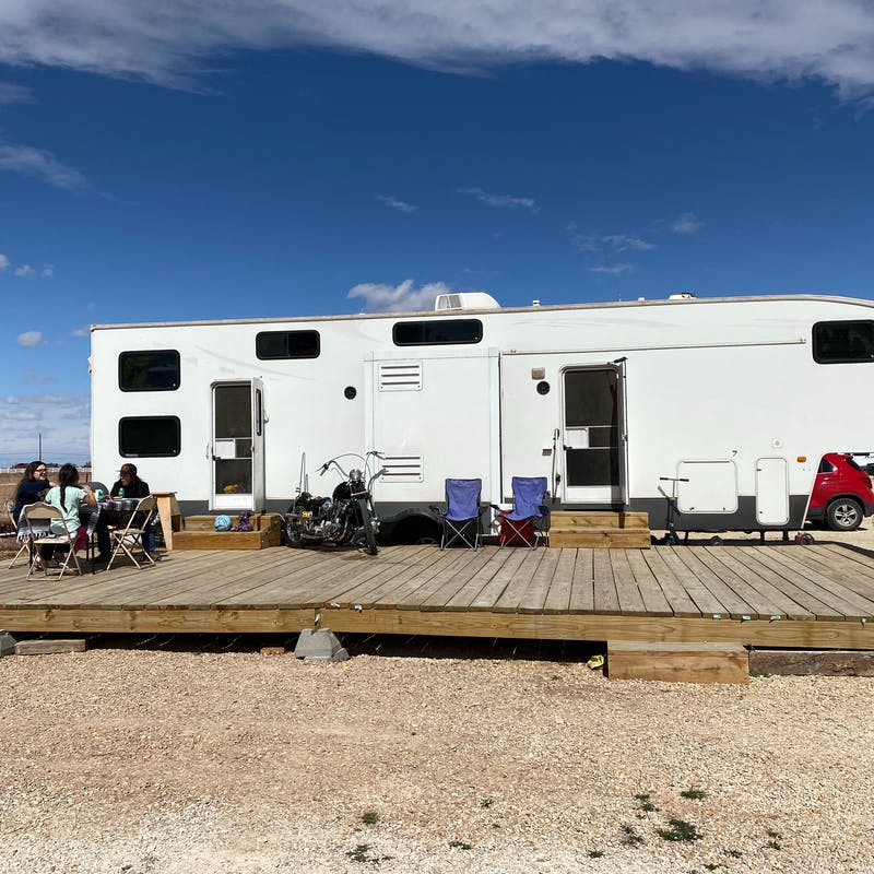 An RV parked at a desert campsite with an outdoor patio.