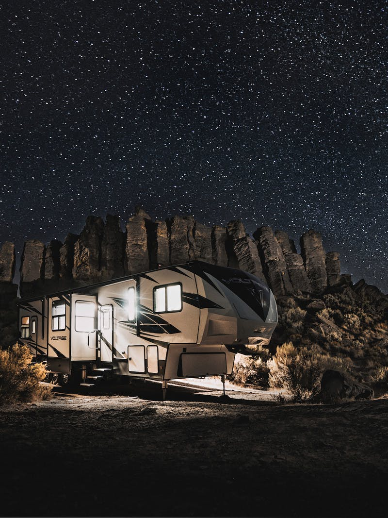 fifth-wheel travel trailer RV underneath dark starry sky at night