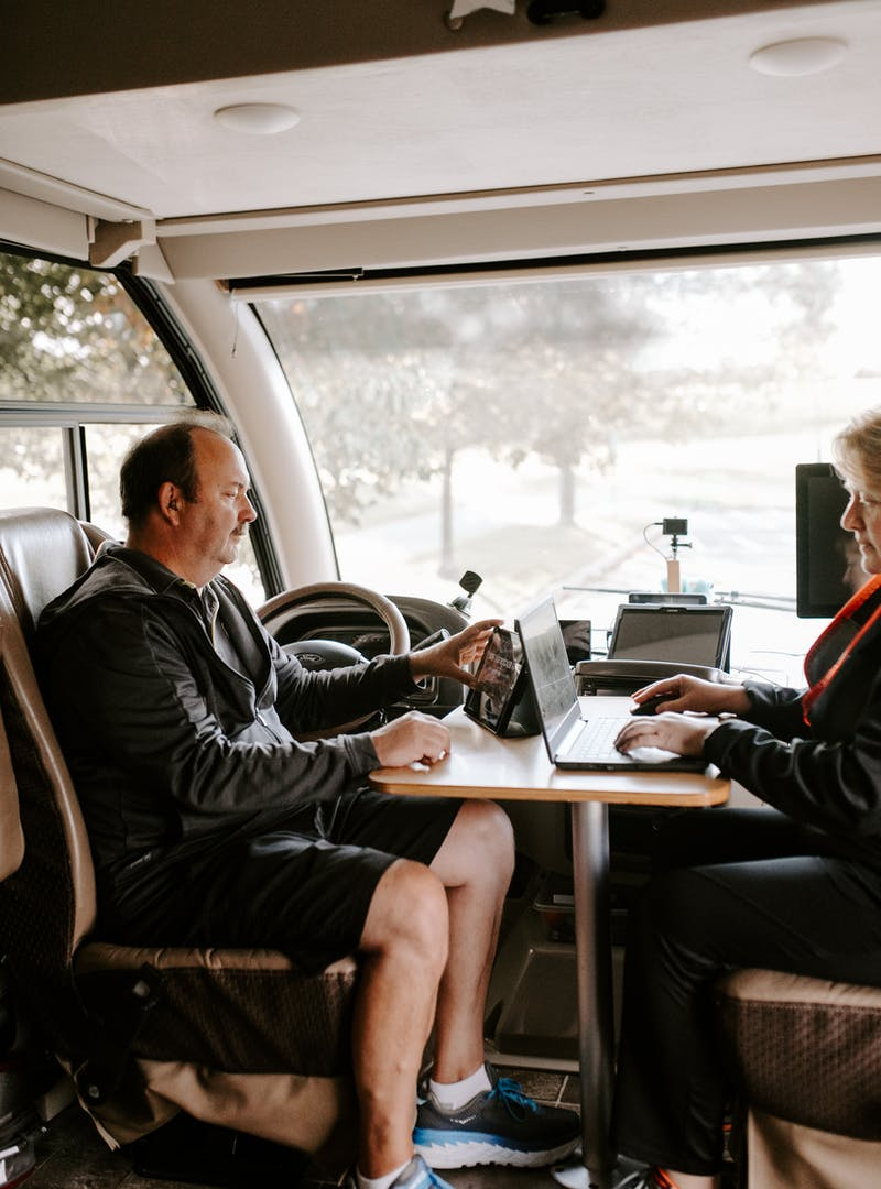 David and Kathy sitting at an RV desk with a laptop and a tablet.