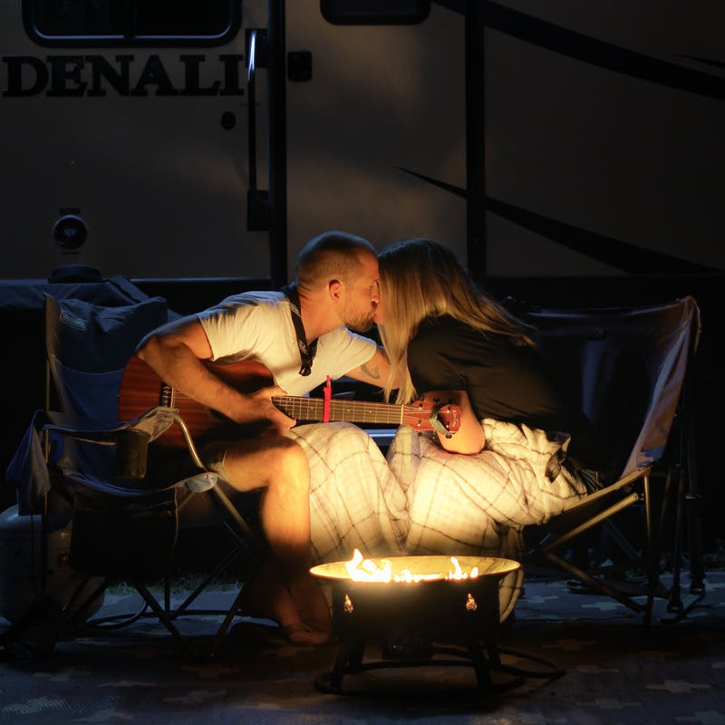 Amick and Christy Cutler kissing in front of a fire.