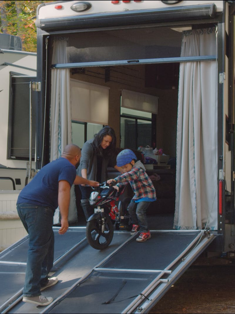 Luis and Sandra helping Julian wheel his bike out of the toy hauler RV.