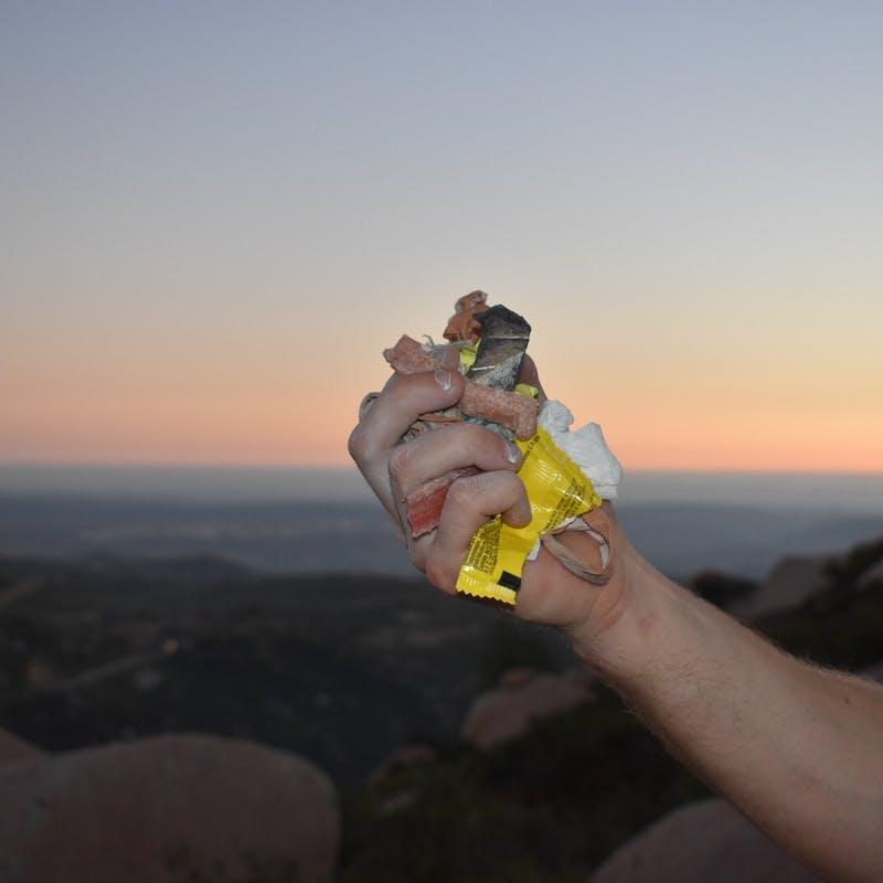 Male hand holding up fistful of trash in front of a sunset