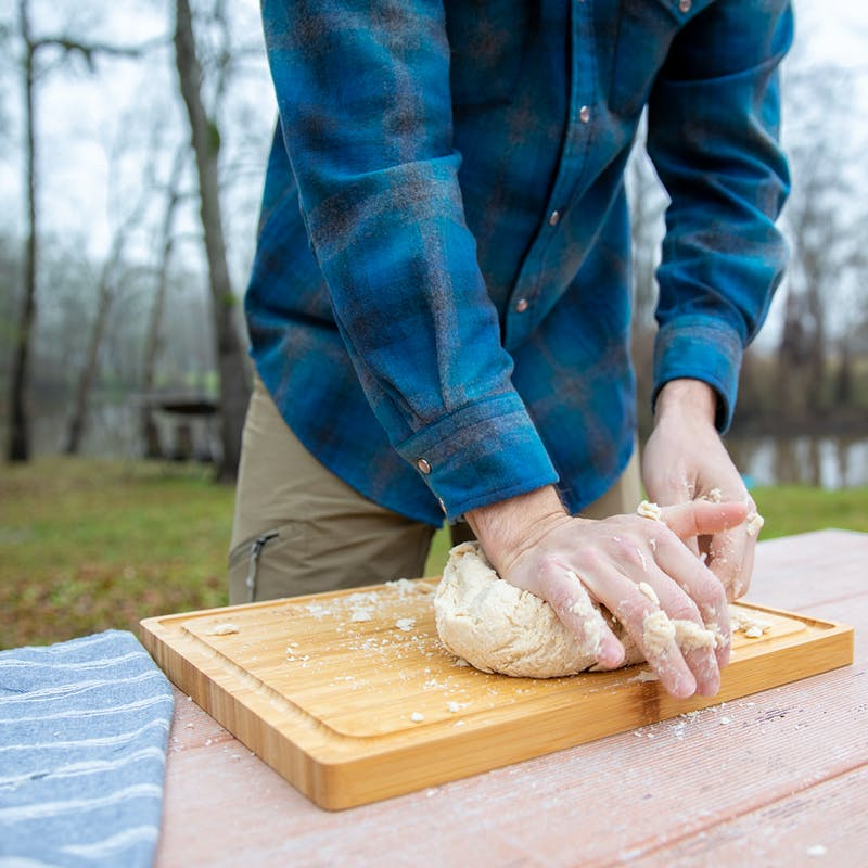 Kneading dough on a cutting board outside.