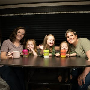 Two moms and triplet daughters around an RV  table drinking milk.