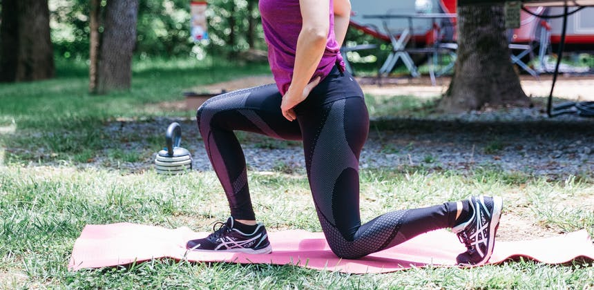 A woman doing lunges on a yoga mat in the grass outside an RV.