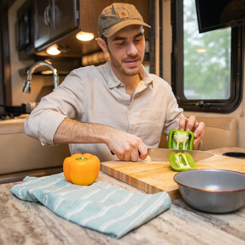 A man cutting a green pepper at an RV kitchen table.