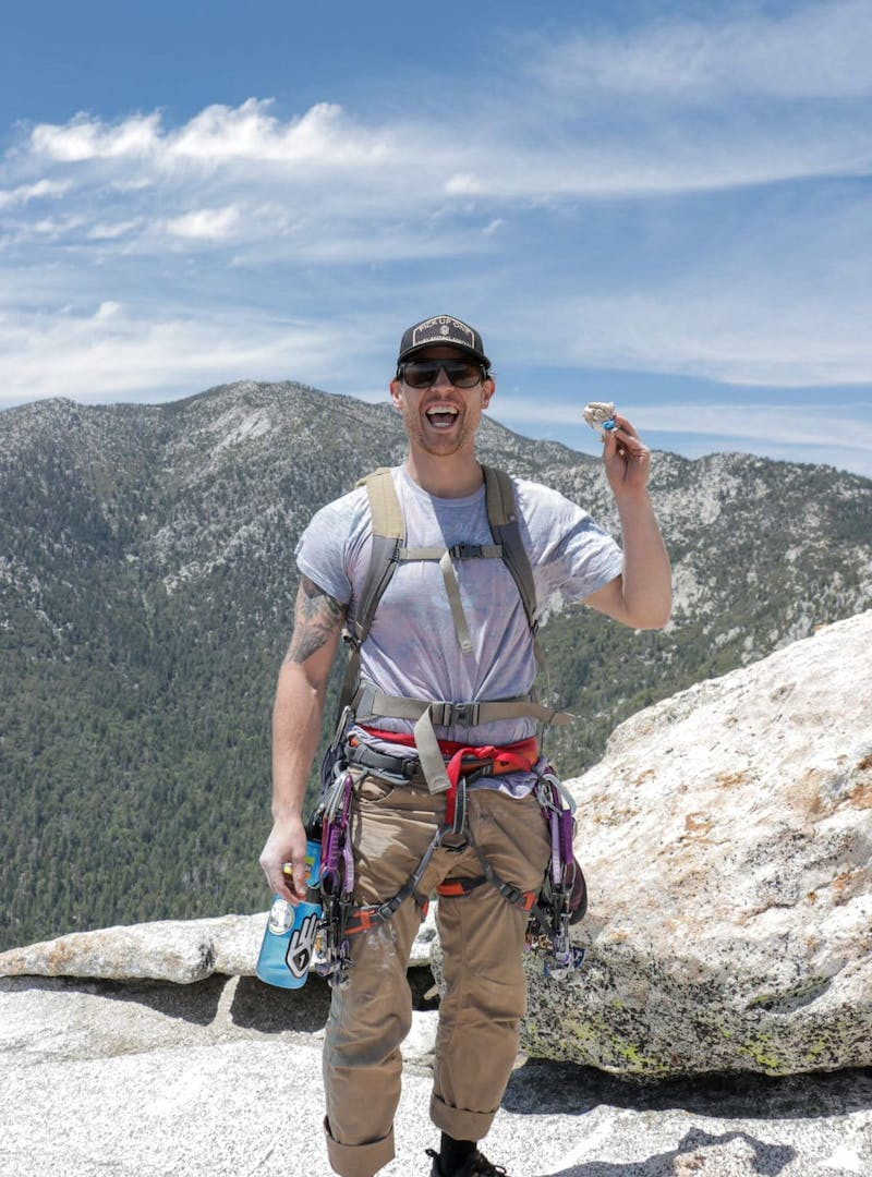 Male rock climber standing on top of mountain, smiling, holding trash