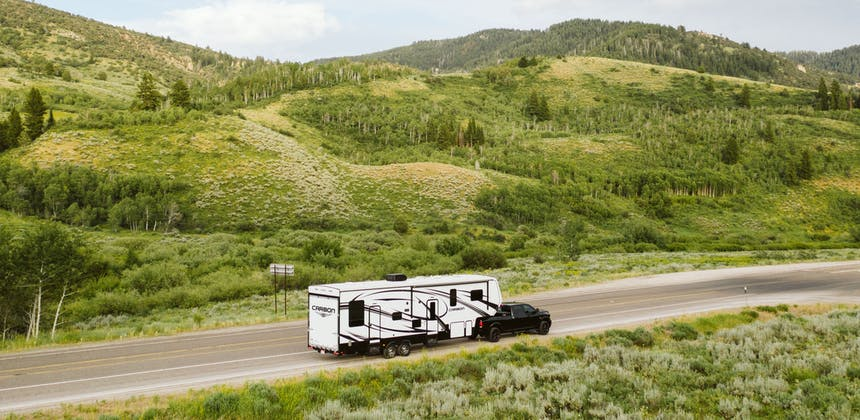 A fifth wheel toy hauler RV driving down a scenic road.