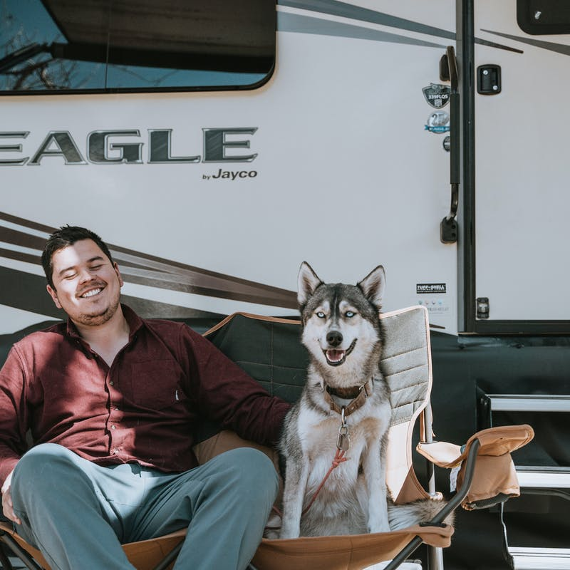 Nico sitting outside the RV with a husky in the chair next to him.