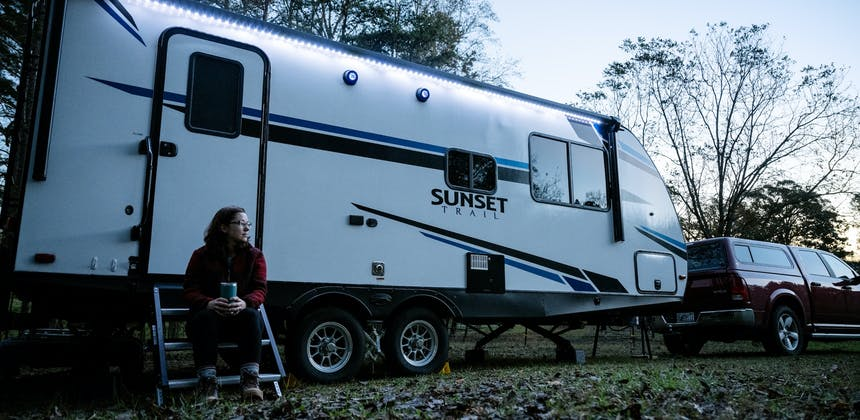 Marcia Schabel sitting on the steps of her Sunset Trail RV in the early morning with a cup of coffee.