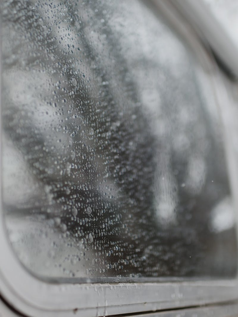 Gray shot, close up of rain and water on the window of an Airstream RV.