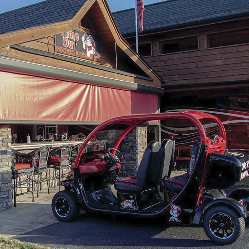 The same tricked-out fancy golf cart parked in front of an elaborate permanent structure at the RV tailgating park.