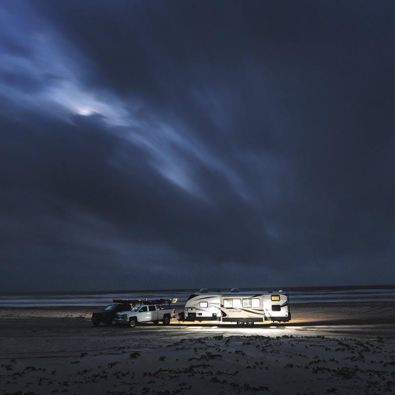 A Keystone Cougar travel trailer RV sits on the beach at nighttime.