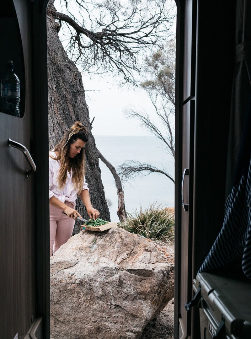 Sarah Glover cutting green beans on a rock outside motorhome door.