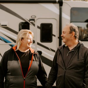 David and Kathy Boland holding hands outside their parked Thor RV.