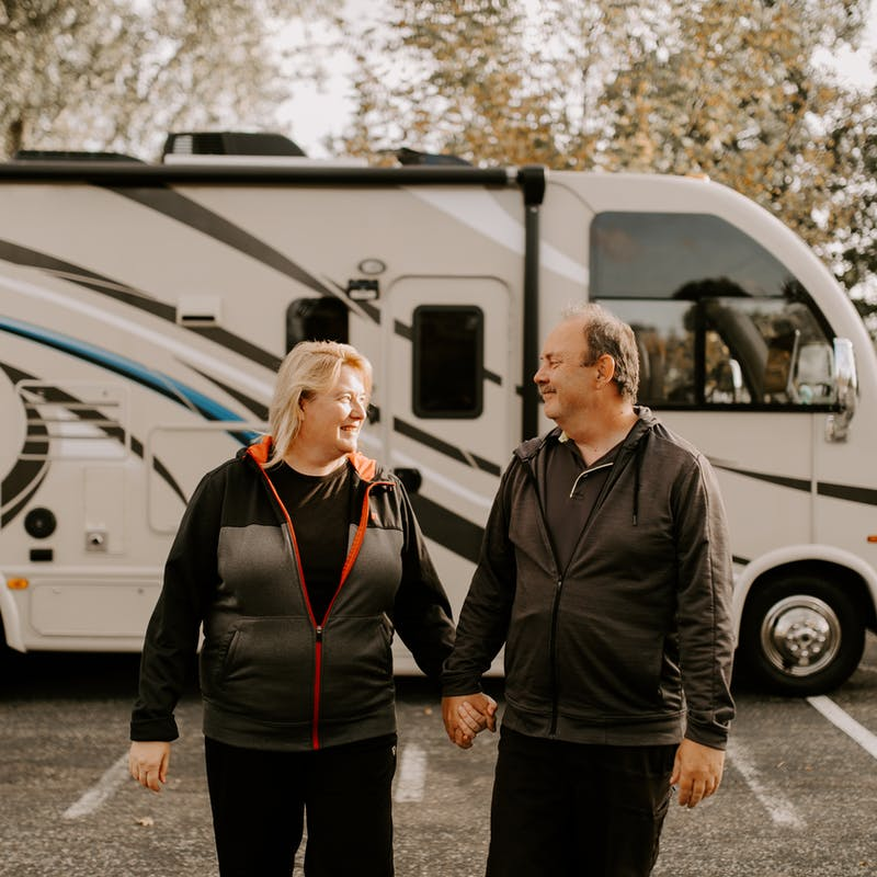 The Bolands holding hands outside their RV.