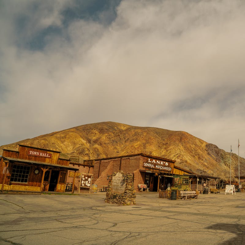 Calico Ghost Town from the parking lot, with old wooden buildings and large brown hills in the background