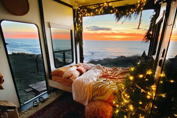 The view out an RV decorated with lights and pine for Christmas, with the window facing the sunset over a beach.