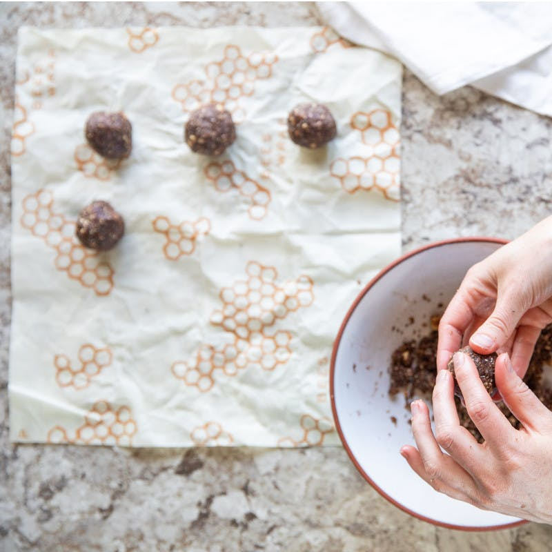 Hands rolling chia seed dough into small balls and placing them on bees' wax paper.
