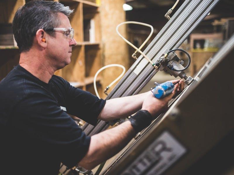 Man works on assembling an RV inside a factory.
