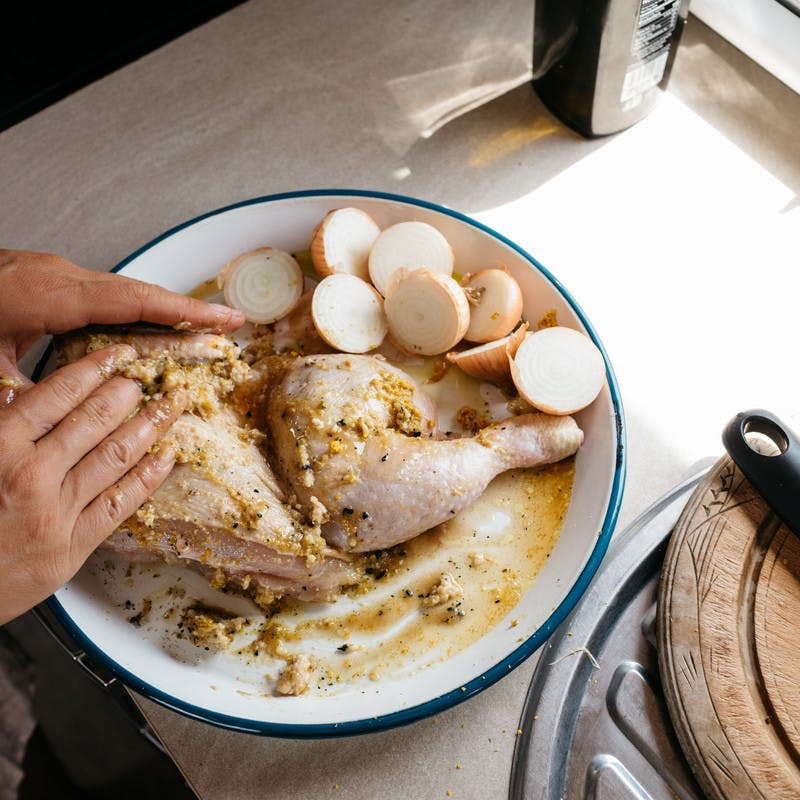 Hands rubbing marinade on raw chicken in a bowl.