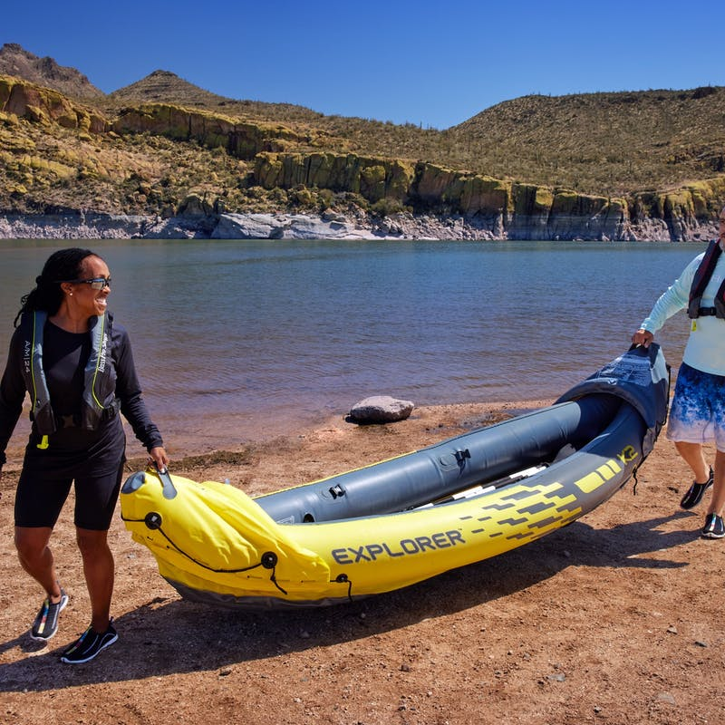 Robin and Warren hold an inflatable kayak by a lake.