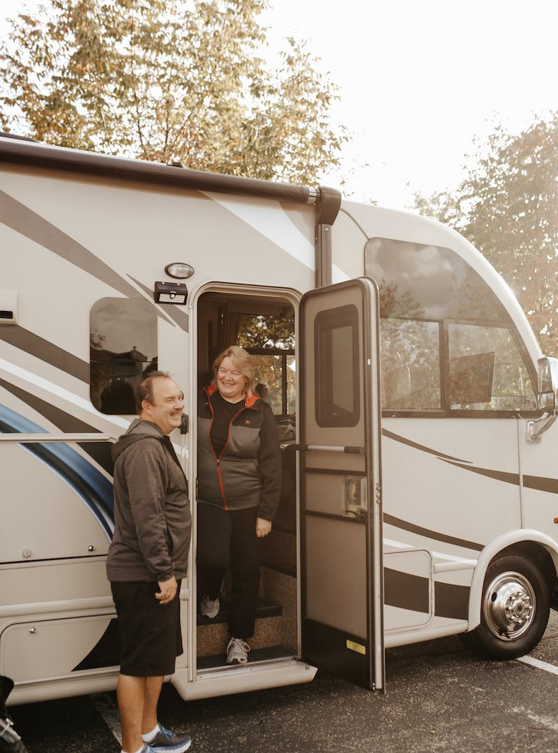 David and Kathy Boland standing in the doorway of their Thor RV.