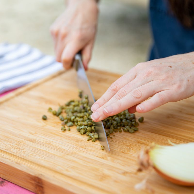 Hands holding a knife that chops capers on a wooden cutting board.