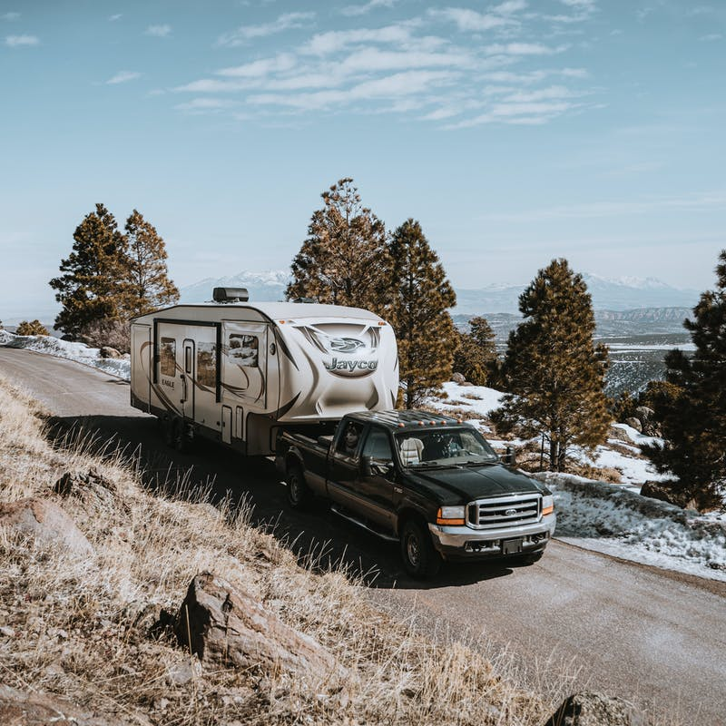 A truck towing a Jayco RV on a mountain road.