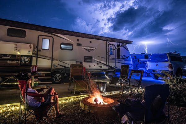 Bill Sferrazza's RV parked at a campsite with family enjoying a campfire at night.