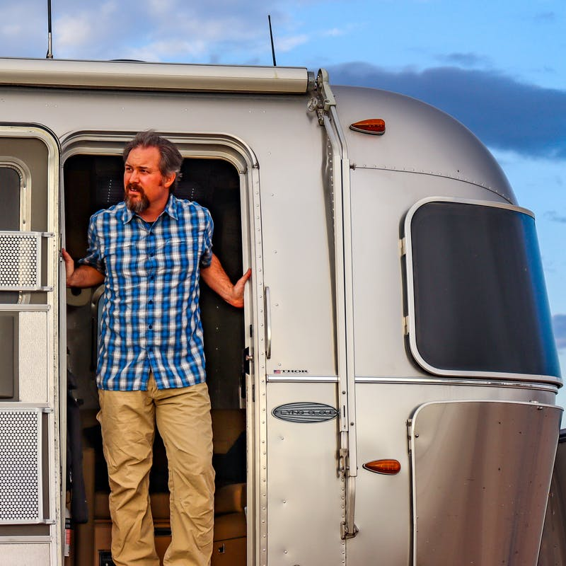 Greg Graham stands at the door of his Airstream.