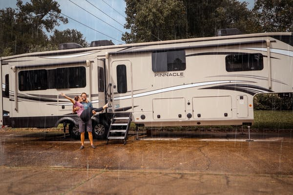 Holly Miner's husband holding her in the rain with their Jayco Pinnacle behind them.