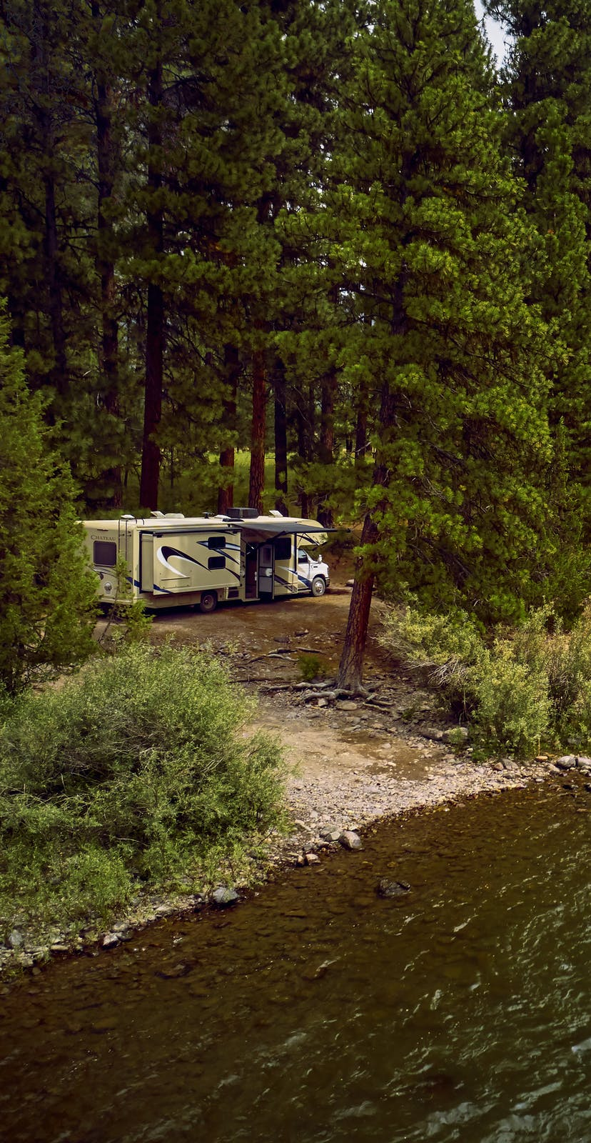An RV parked next to a river.